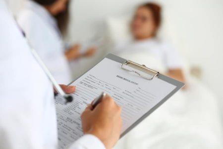 Female Medicine Doctor Filling In Patient Medical History List
